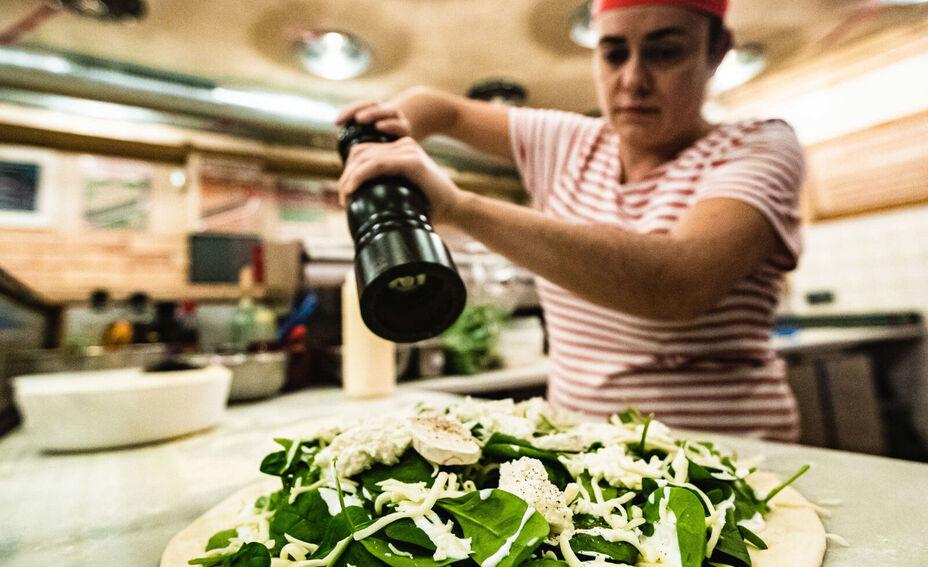 Cocinera de la Pizzeria Tombola con el pimentero sobre una pizza en Burgos