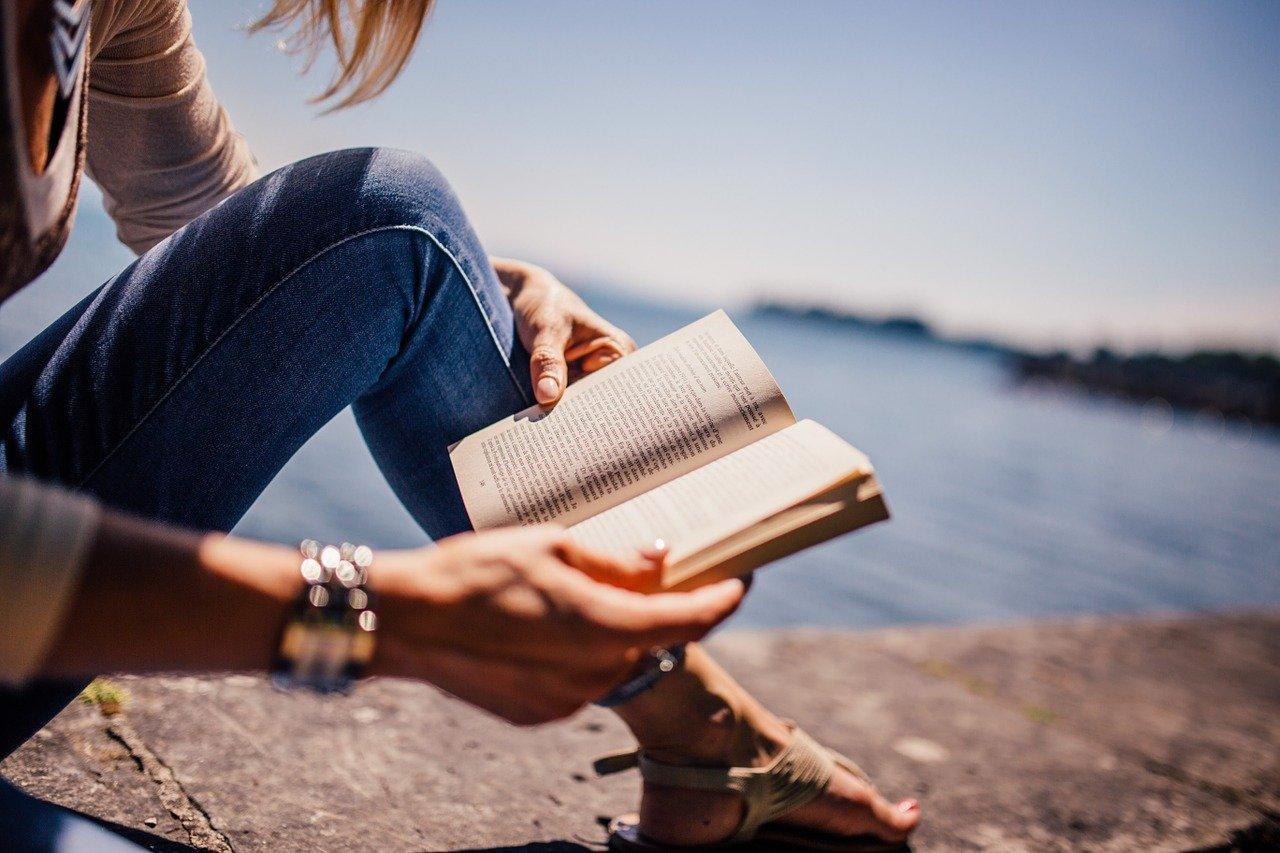 Persona leyendo un libro al mar en el Día del Libro en Burgos